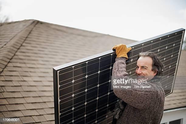A man carrying a large solar panel across a farmyard.
