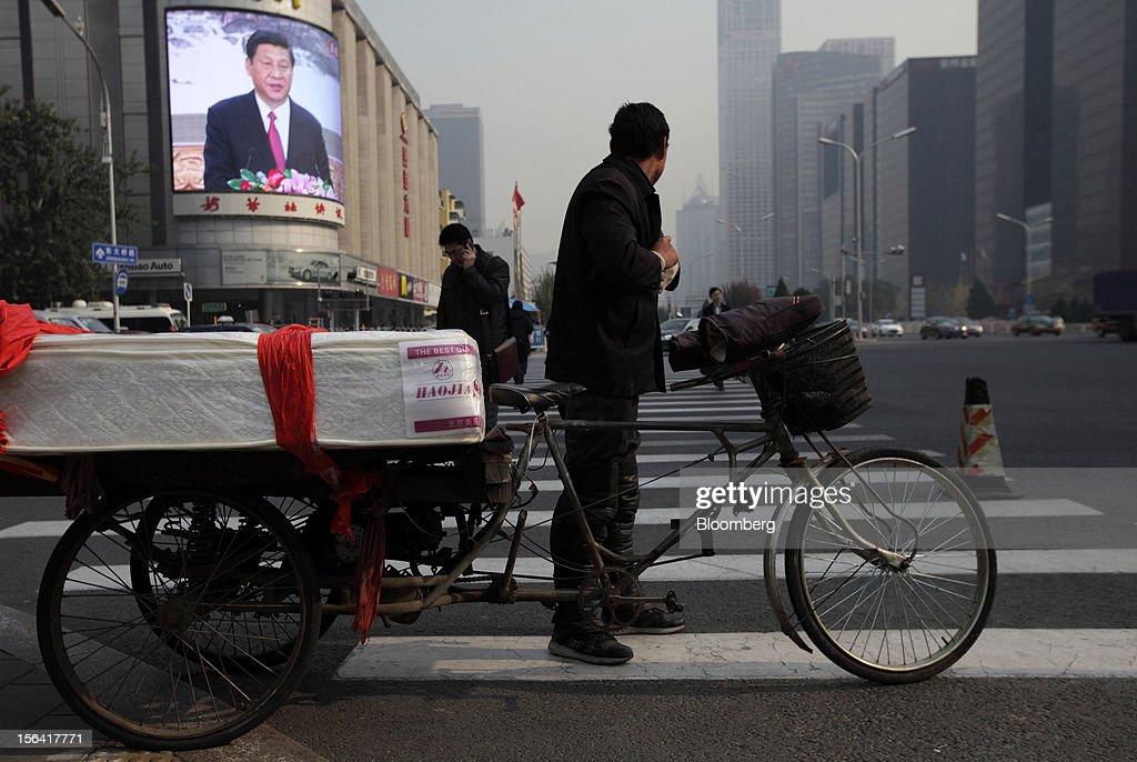 A man carrying a mattress on a bicycle looks at a monitor broadcasting a news conference by Xi Jinping, general secretary of the Communist Party of China, outside a subway station in Beijing, China, on Thursday, Nov. 15, 2012. Xi replaced Hu Jintao as head of the Chinese Communist Party and the nation's military, ushering in the fifth generation of leaders who are set to run the world's second-biggest economy over the next decade. Photographer: Tomohiro Ohsumi/Bloomberg via Getty Images