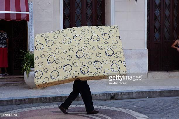 A man carrying a mattress