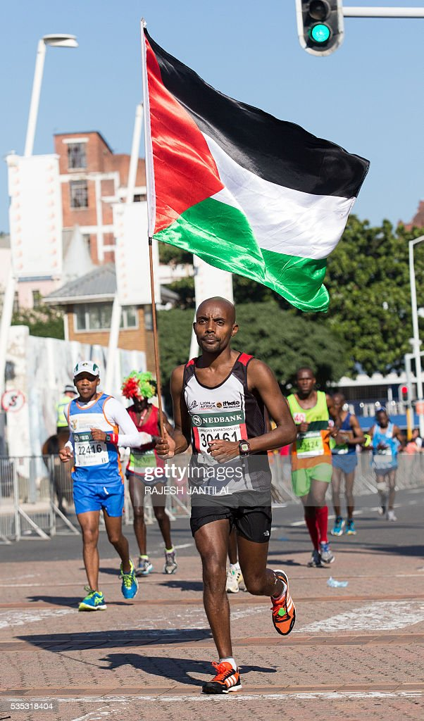 A man, carrying a Palestinian flag, runs along with other 21,000 competitors from South Africa and abroad the 89,2 kilometres ultra distance Comrades Marathon from Pietermaritzburg to Durban on May 29, 2016. It is regarded as one of the most gruelling ultra marathon in the world. / AFP / RAJESH