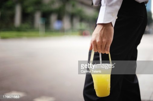 Man carrying a plastic cup of lime juice : Stock Photo