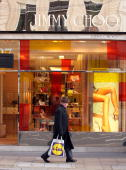 A man carrying a shopping bag from the discount food retailer Lidl walks past the designer shoe shop 'Jimmy Choo' on New Bond Street on November 22...