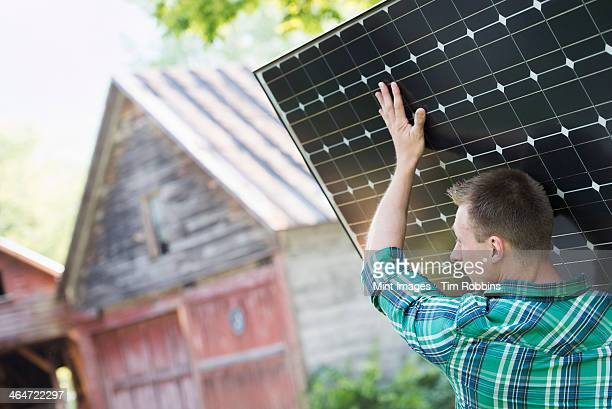 A man carrying a solar panel towards a building under construction.