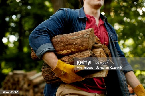A man carrying a stack of logs under his arm.