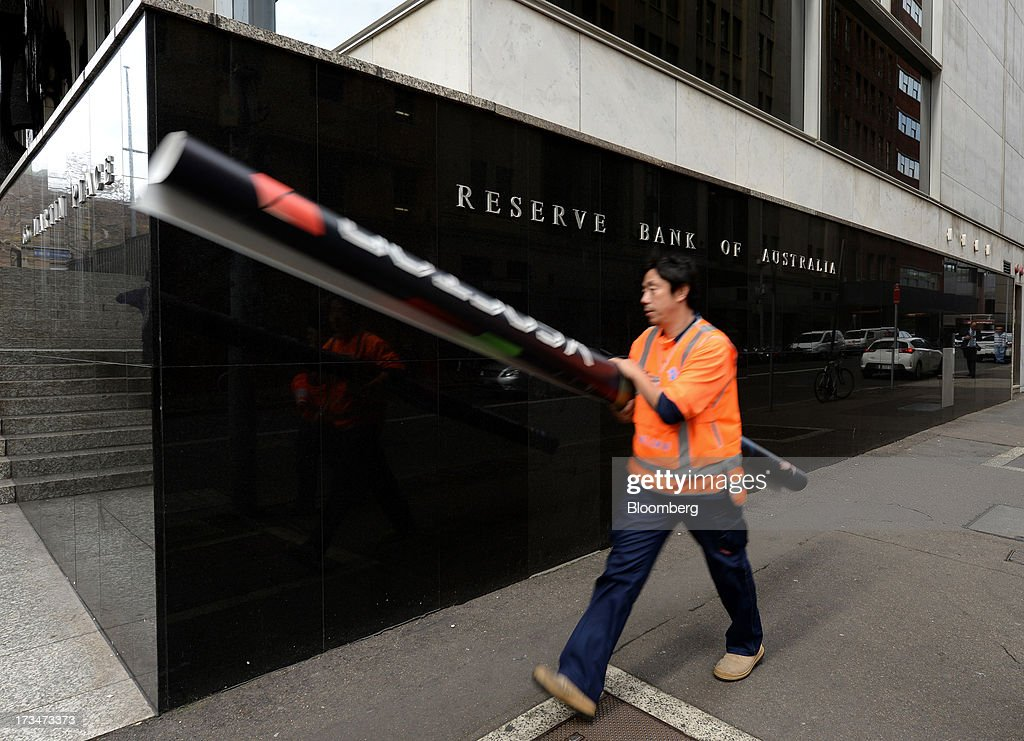 A man carrying a tube container walks past the Reserve Bank of Australia (RBA) headquarters in the central business district of Sydney, Australia, on Monday, July 15, 2013. While the RBA previously needed higher interest rates to control price pressures as the Australian economy expanded since 1991 without a recession, Governor Glenn Stevens has slashed the cash target, predicting a mining boom will wane. Photographer: Dan Himbrechts/Bloomberg via Getty Images