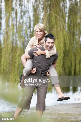 Man carrying a woman on his back, in a park. : Stock Photo