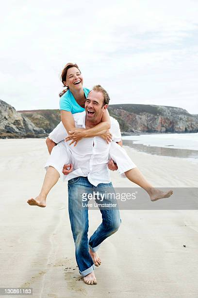 A man carrying a woman piggy back on the beach
