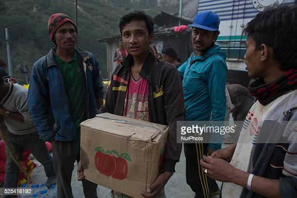 A man carrying an apple box come from China who was leave as a waste inside a destroyed Chinese truck on the Araniko Road near the Kobani Village...