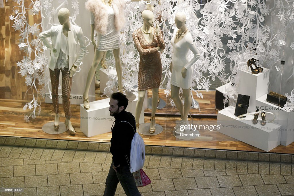 A man carrying an Apple Inc. shopping bag walks past a BCBG Max Azria Group Inc. store at the Fair Oaks Mall in Fairfax, Virginia, U.S., on Monday, Nov. 12. 2012. Sales at U.S. retailers probably fell in October for the first time in four months economists said before a report on Nov. 14. Photographer: Andrew Harrer/Bloomberg via Getty Images