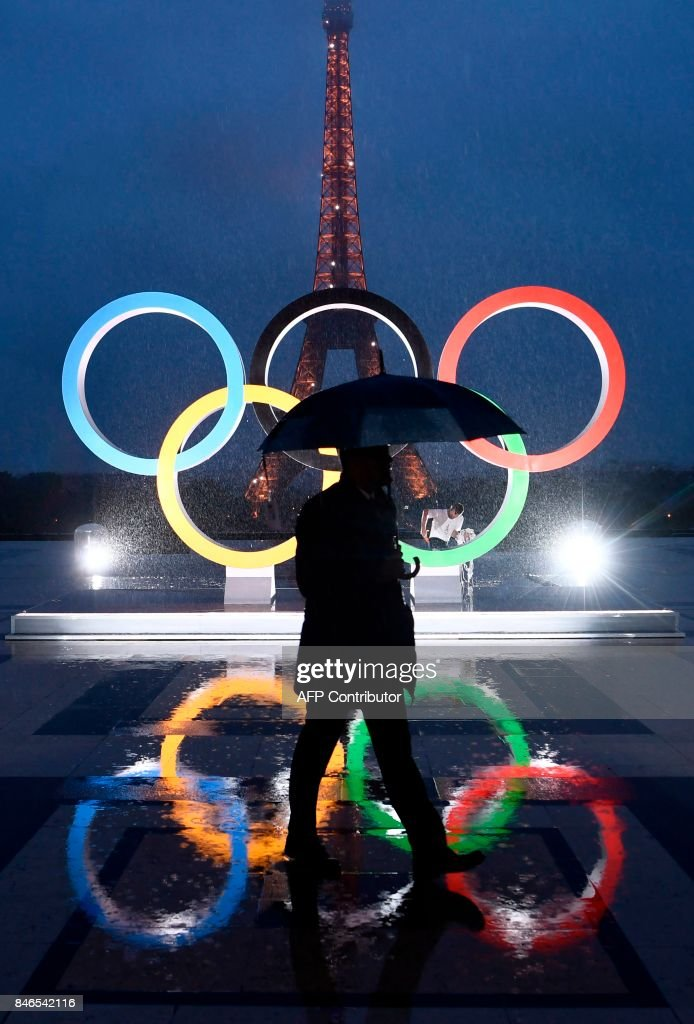 A man carrying an umbrella walks past the Olympics Rings on the Trocadero Esplanade near the Eiffel Tower in Paris, on September 13, 2017, after the International Olympic Committee named Paris host city of the 2024 Summer Olympic Games. The International Olympic Committee named Paris and Los Angeles as hosts for the 2024 and 2028 Olympics on September 13, 2017, crowning two cities at the same time in a historic first for the embattled sports body. /