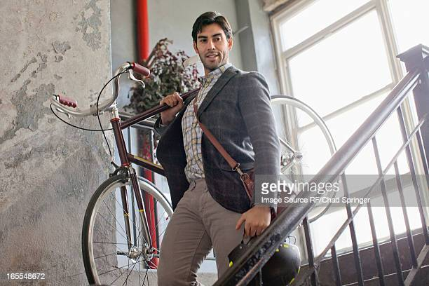 Man carrying bicycle down staircase