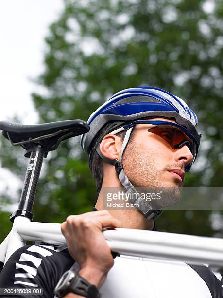 Man carrying bicycle on shoulder, low angle view, close-up