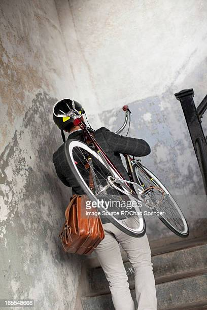Man carrying bicycle up staircase