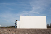 Man carrying block and building wall outdoors