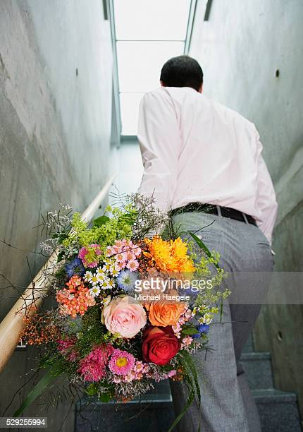 Man Carrying Bouquet of Flowers Up Stairway