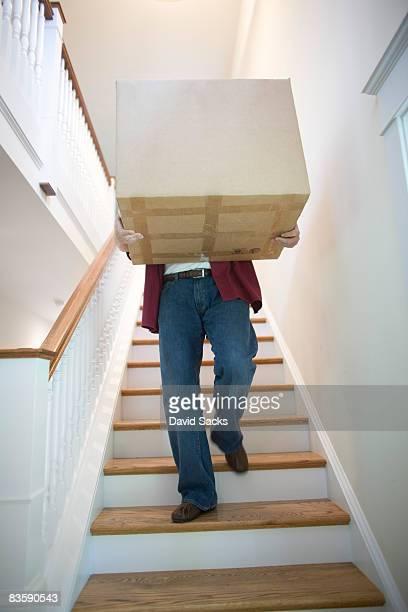 Homem descer escadas de caixa de transporte