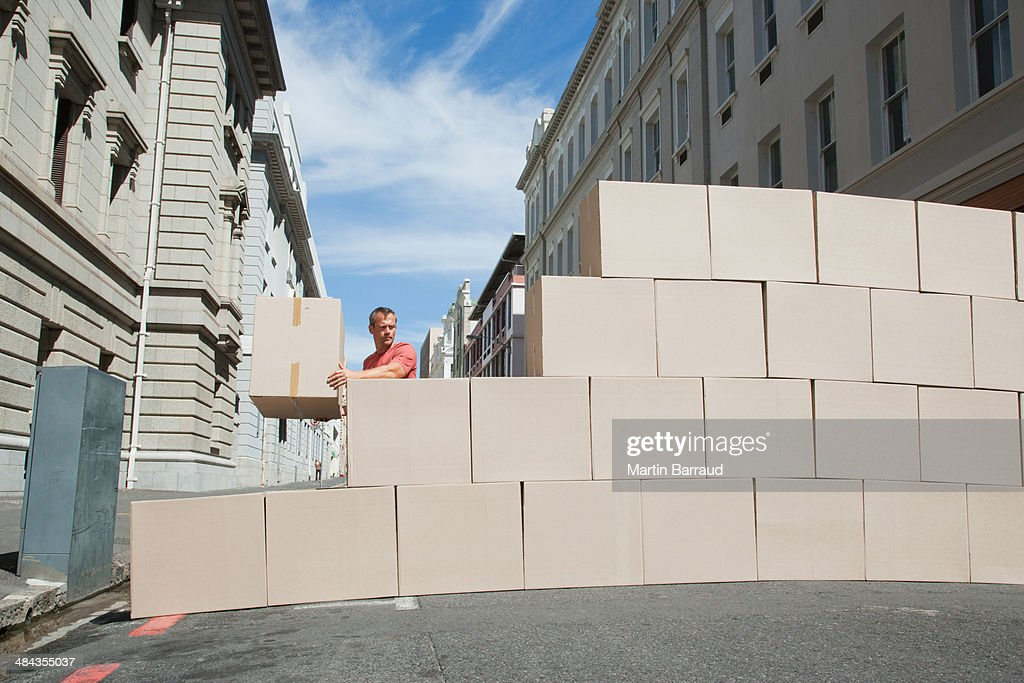 Man carrying box in roadway : Stock Photo