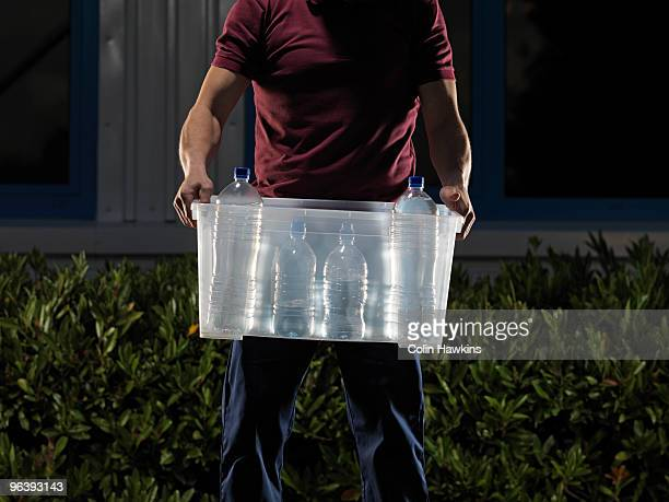 man carrying box of water at night