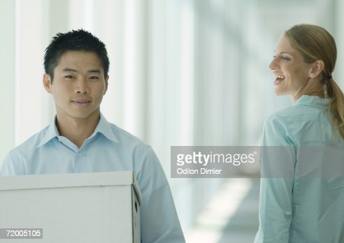 Man carrying boxes in hallway, female colleague watching