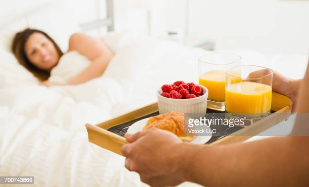 Man carrying breakfast for woman in bed