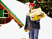 Man carrying bundle of firewood outside of cabin
