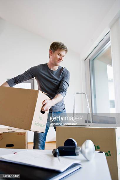 Man carrying cardboard boxes in house