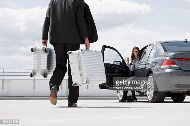 man carrying cases woman waiting in car