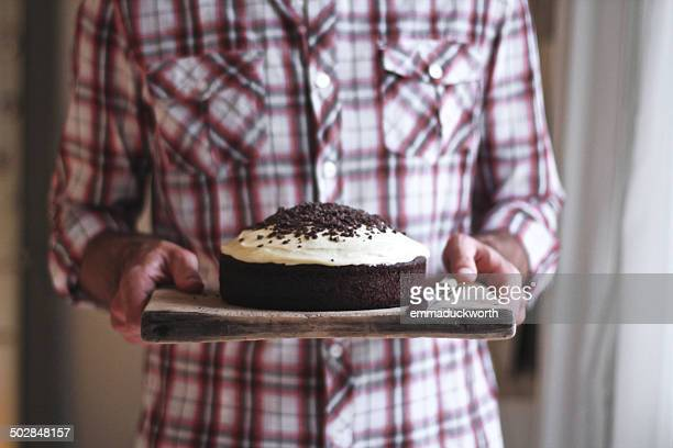 Man carrying chocolate cake on wooden board