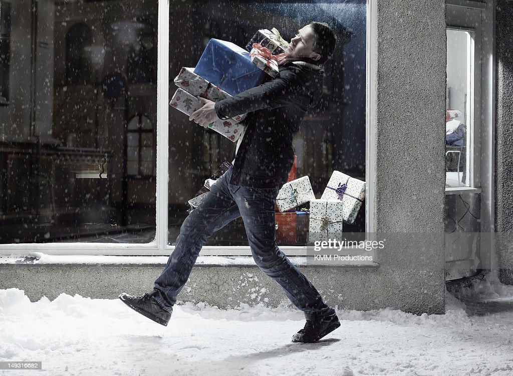 Man carrying Christmas gifts in snow : Stock Photo