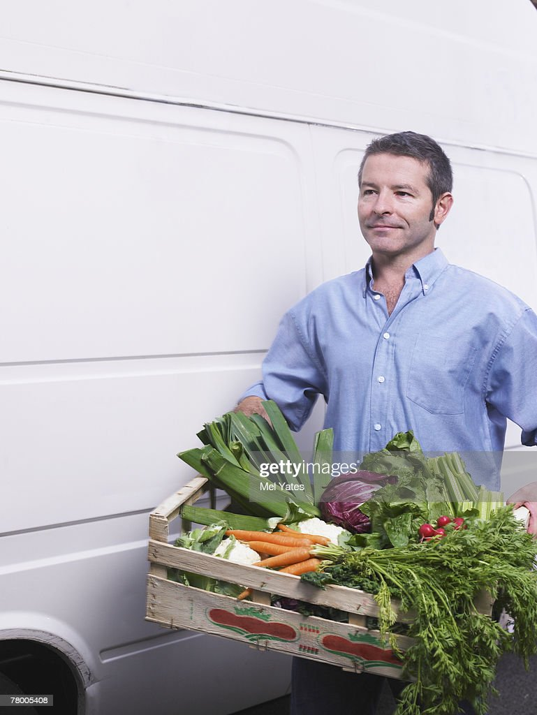 Man carrying crate of vegetables from van : Stock Photo