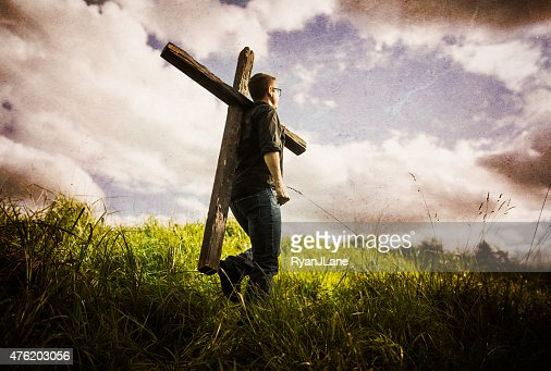 http://media.gettyimages.com/photos/man-carrying-cross-of-christ-on-his-shoulder-picture-id476203056?s=170667a