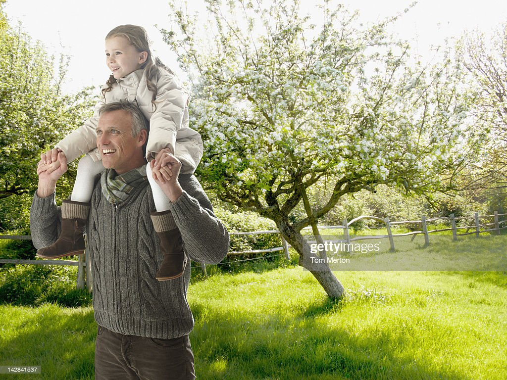 Man carrying daughter on his shoulders outdoors : Stock Photo
