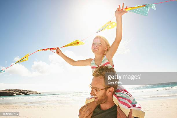 Man carrying daughter (6-8) on shoulders