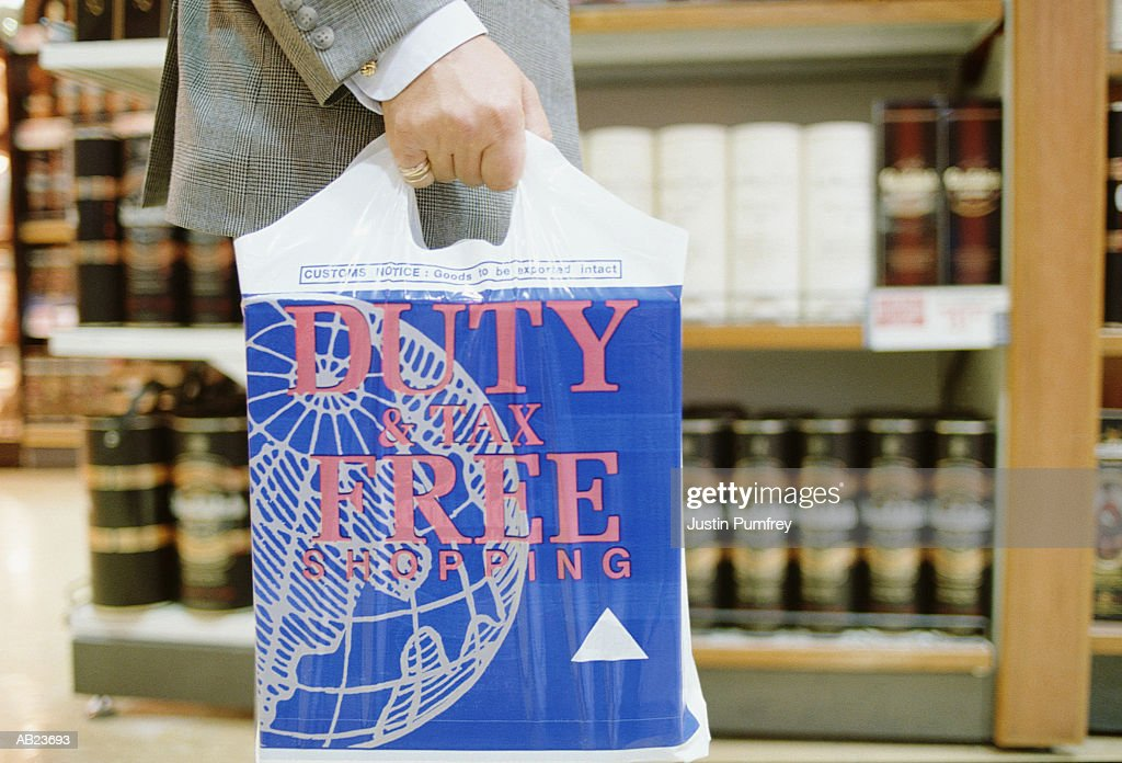 Man carrying 'duty free' carrier bag, mid-section : Photo