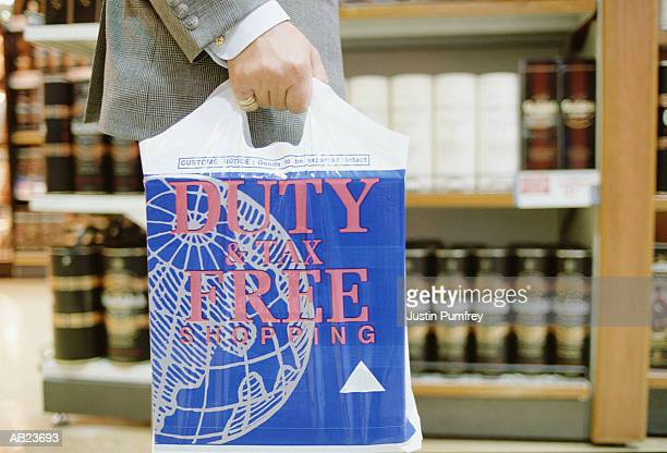 Man carrying 'duty free' carrier bag, mid-section