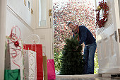 Man carrying fir tree into house, shopping bags in hall,low angle view
