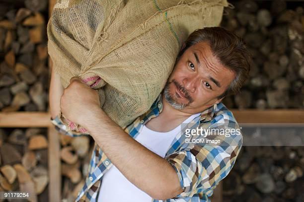 Man carrying firewood on shoulder