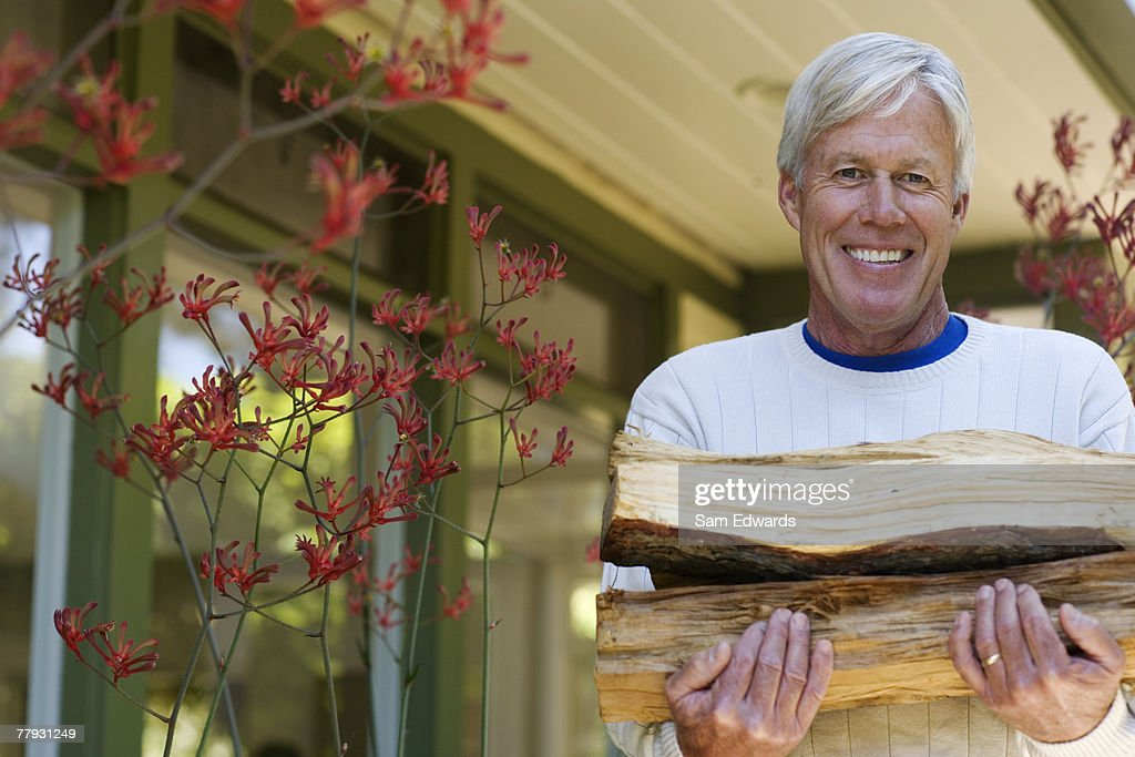 Man carrying firewood smiling : Stock Photo
