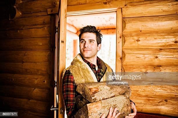 Man carrying firewood through doorway