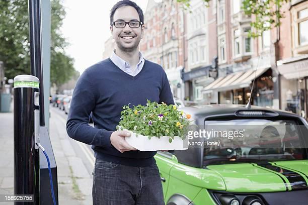 Man carrying flowerbox on city street