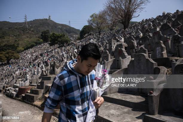 A man carrying flowers walks past tombstones at a cemetery ahead of the Ching Ming Festival or gravesweeping day in Hong Kong on April 2 2017...