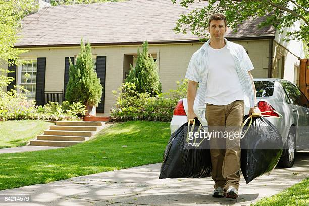 Man Carrying Garbage Bags on Drive