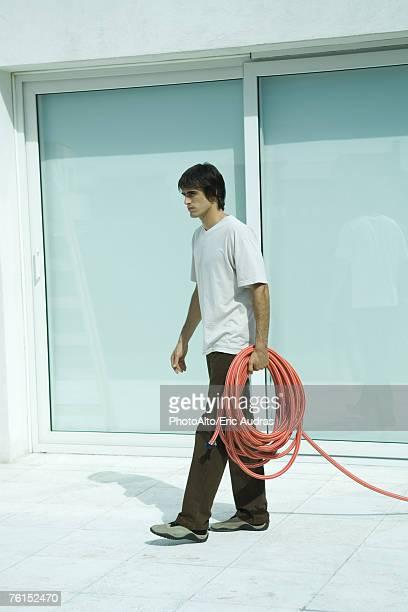'Man carrying garden hose, full length'