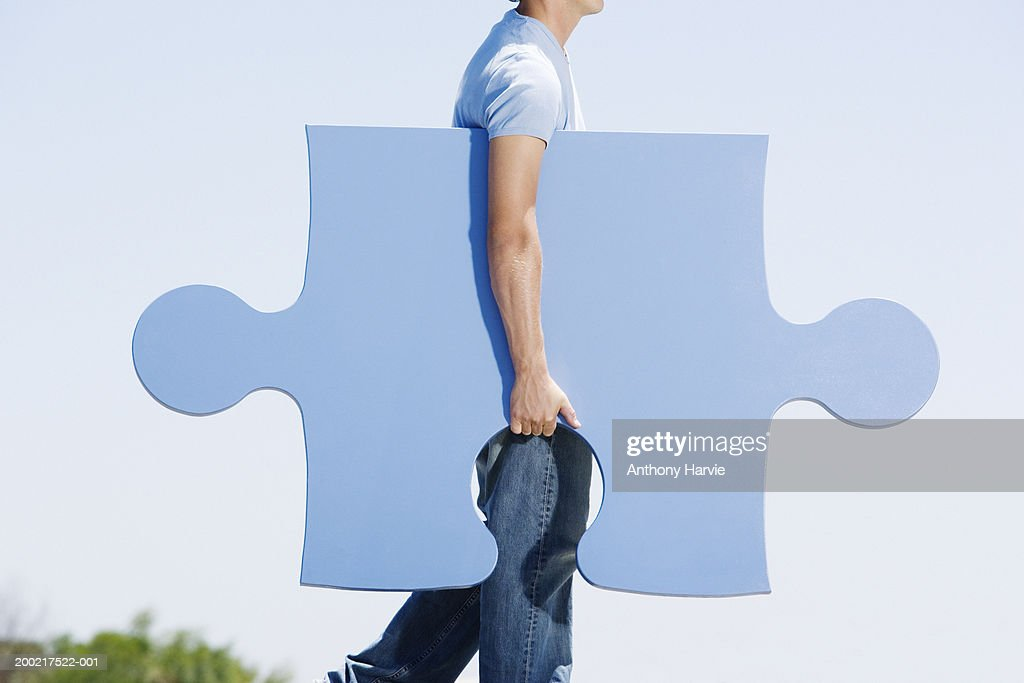 Man carrying giant jigsaw piece under arm, side view : Stock Photo