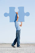 Man carrying giant jigsaw puzzle piece on shoulder, side view