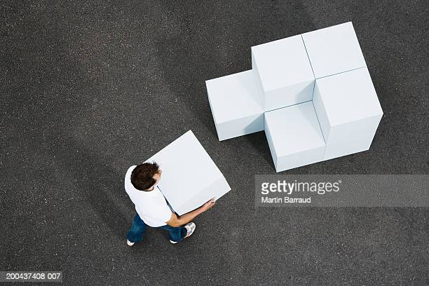 Man carrying giant white cube towards stacked cubes, elevated view