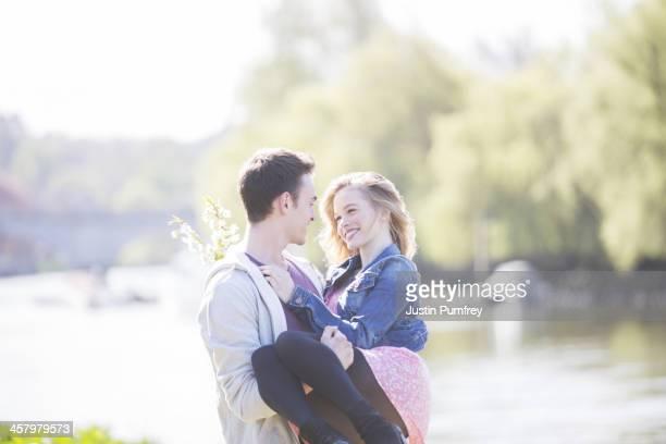 Man carrying girlfriend along river