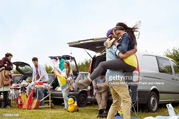 Man carrying girlfriend at yard sale