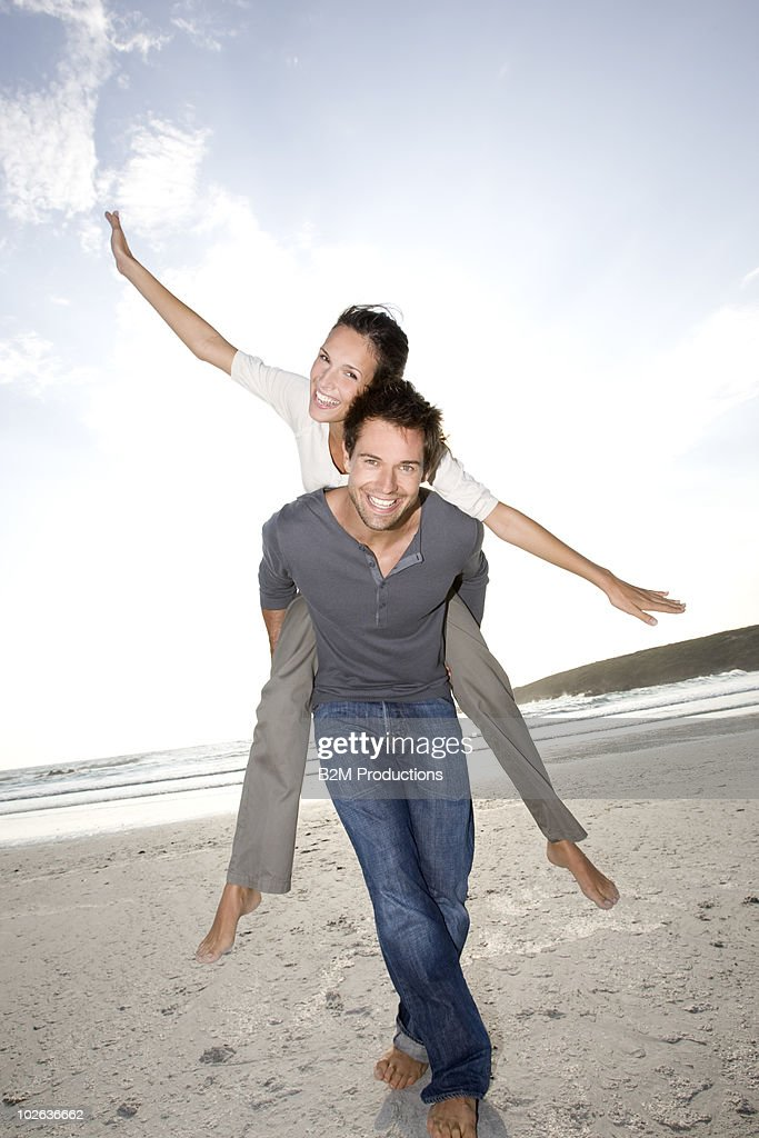 Man carrying girlfriend by the sea, Portrait : Stock Photo
