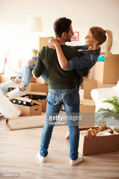 Man carrying girlfriend in new home. Debica, Poland